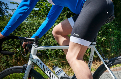 Side view of a ProBikeKit cyclist on a road bike wearing black PBK cycling shorts and a blue and white PBK long sleeved jersey
