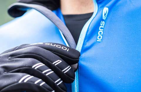 Cyclist wearing black Sugoi cycling gloves, zipping up a blue Sugoi cycling jacket