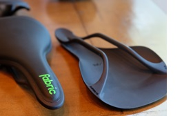 Two black Fabric saddles sitting on a wooden surface - the one on the right is placed upside down with the seat on the surface, next to the left saddle placed the correct way up