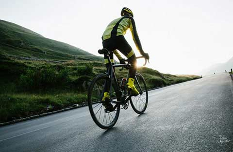 View of the back of a cyclist riding up hill in a reflective cycling jersey and tights