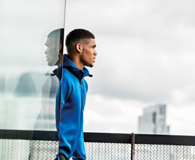 Side profile of a male model wearing a blue adidas sweatshirt