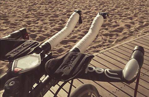 Bike with time-trial handlebars on some decking on a beach