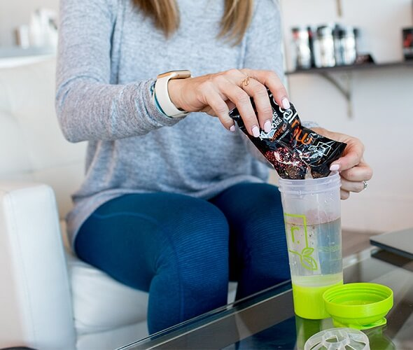 A women emptying an IdealRaw sample pack into a IdealRaw shaker