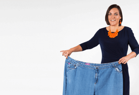 Woman posing with her old jeans after her weight loss