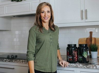 Lisa stood next to two tubs of IdealRaw protein