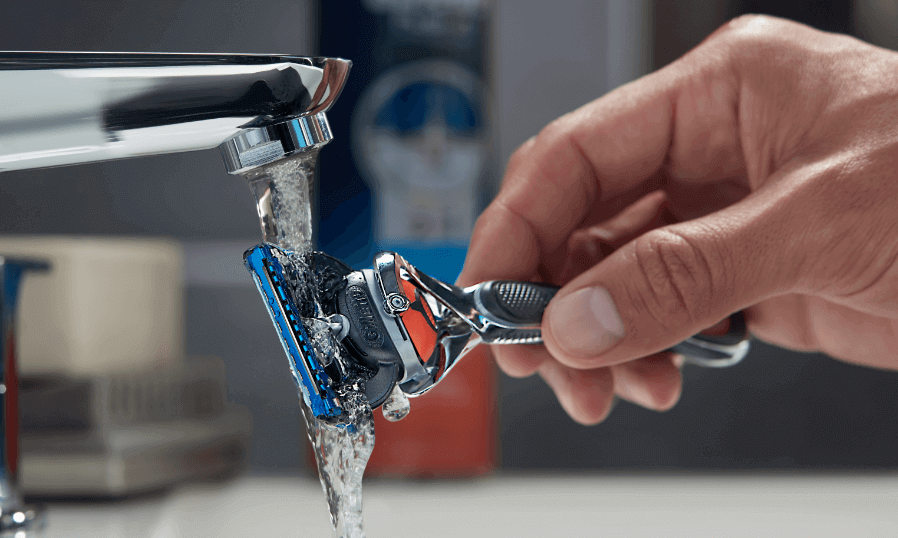 Man rinsing Gillette Fusion5 Proglide under tap.