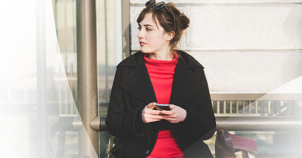 Young woman on phone at a bus stop.