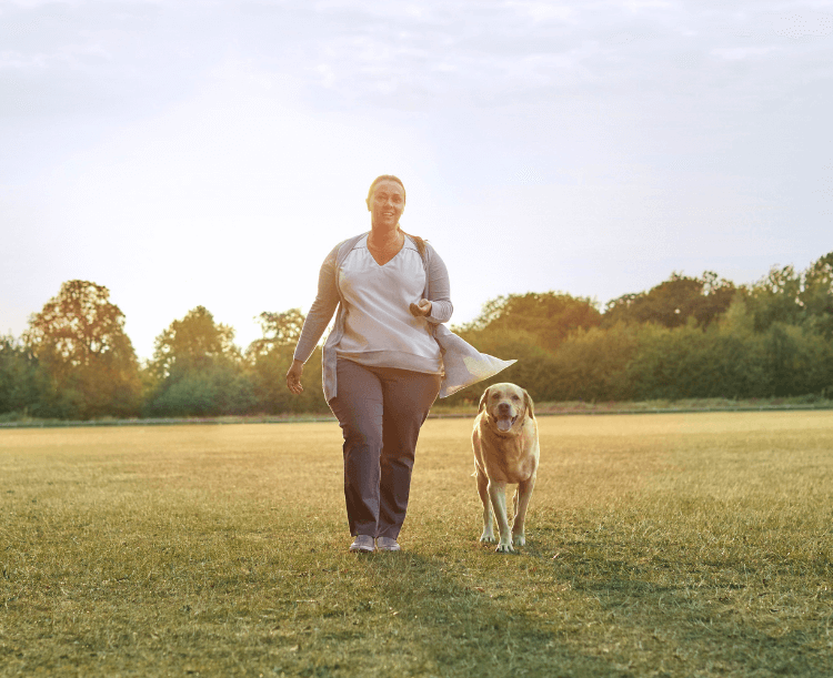Image of Woman walking her dog in the park