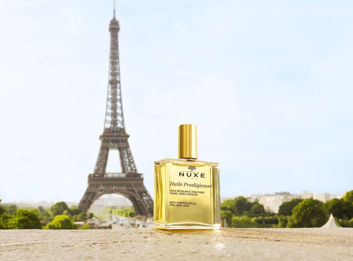 Golden Huile Prodigieuse Bottle in front of the Eiffel Tower