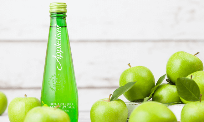 Bottle of Appletiser surrounded by green apples