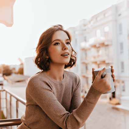 Woman enjoying a coffee on a balcony