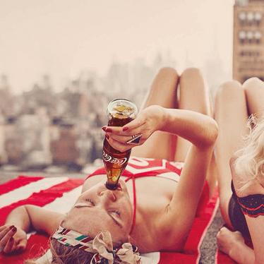Woman enjoying a bottle of coke on a roof top