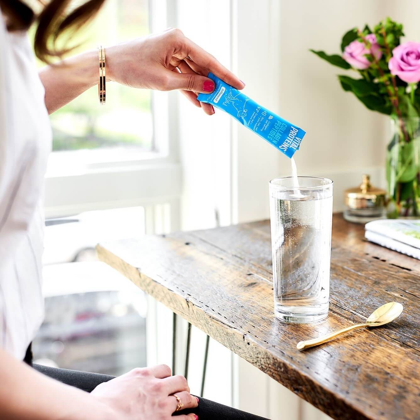Women pouring collagen sachet into glass of water