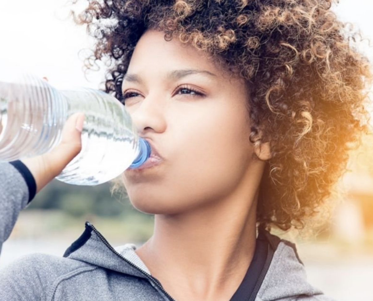 Determined woman drinking a bottle of water