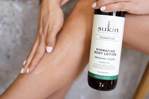 Lady putting on signature Hydrating Body Lotion on leg with bottle showing on the right hand side of the image.