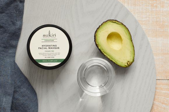 Sukin hydrating facial masque with half and avocado and glass of water for decoration.