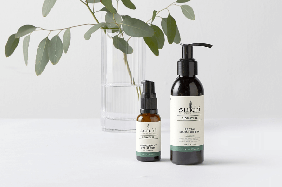Sukin Siganture facial moisturiser and antioxidant eye serum on background with jug of water behind it and a plant leaf.
