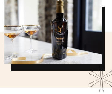Glenfiddich Gran Cru 23 year old Single Malt on a countertop, with a bottle and 2 glasses, ready to drink